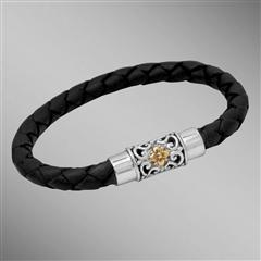 Black woven leather bracelet with gold flower on silver clasp.  Arista.